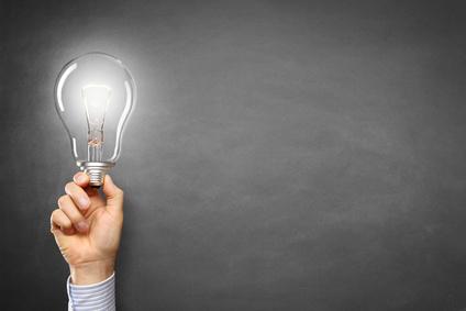 Hand mit Lampe vor einer Tafel